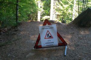 """Warndreieck mit der Aufschrift """"Achtung Hier wird gebaut. Bitte langsam fahren"""" steht auf einem Waldweg"""