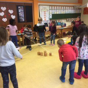 Foto von Kinder, welche im Klassenzimmer im Kreis stehen. Jedes Kind hat eine Schnur in der Hand. Alle Schnüre enden an einer Konstruktion in der Kreismitte mit der Bauklötze hochgehoben und transportiert werden können.