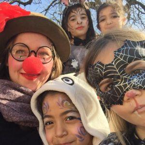 Foto von einer mit roter Clownsnase und Hut ausgestatteten Frau mit vier Kindern, welche ebenfalls Fasnachtsschminke im Gesicht haben.