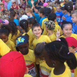 Foto von Schulkindern mit gelben T-Shirts vom Förderverein der Meerwein-Grundschule in einer großen Menge an Kindern beim Stadtlauf Emmendingen