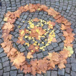 Foto eines rundes Mandala aus braunen und gelben Laubblätter welches auf den Pflastersteinen am Boden liegt
