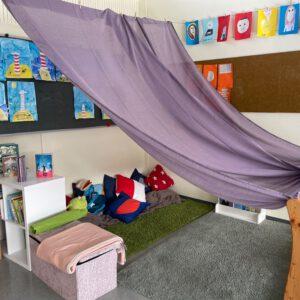 Bild von einer Leseecke in einem Klassenzimmer mit Teppchen, Kissen, Büchern udn einem lila Tuch als Himmel. Außerdem hängen selbst gezeichnete Bilder von Leuchttürmen und Portraits an der Wand