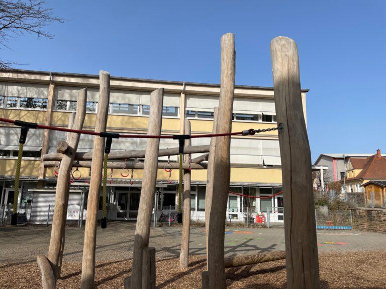 Schulgebäude mit Klettergerüst im Vordergrund